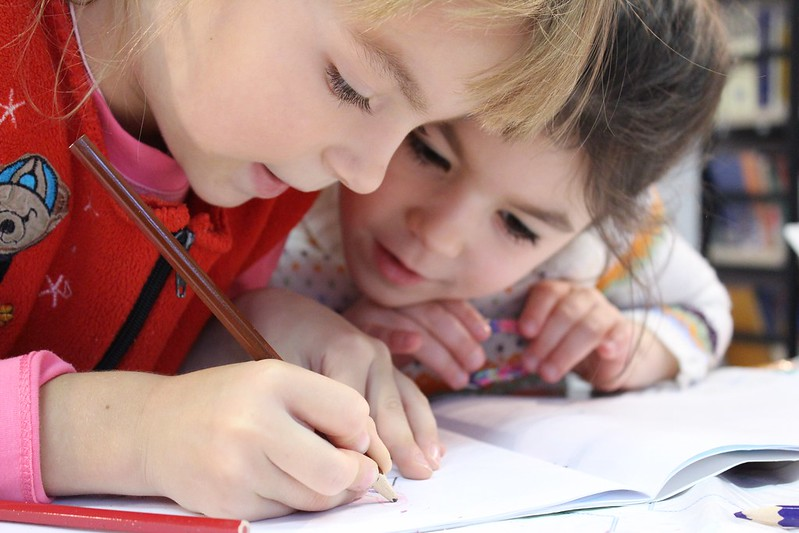Girls looking at notebook of example determiners