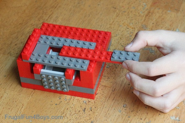 Slot a 2x10 piece attached to a 2x4 piece into your awesome lego candy dispenserd