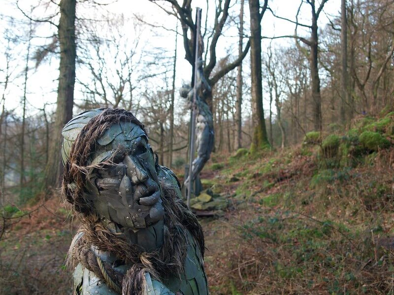 metallic sculpture of a person in a forest