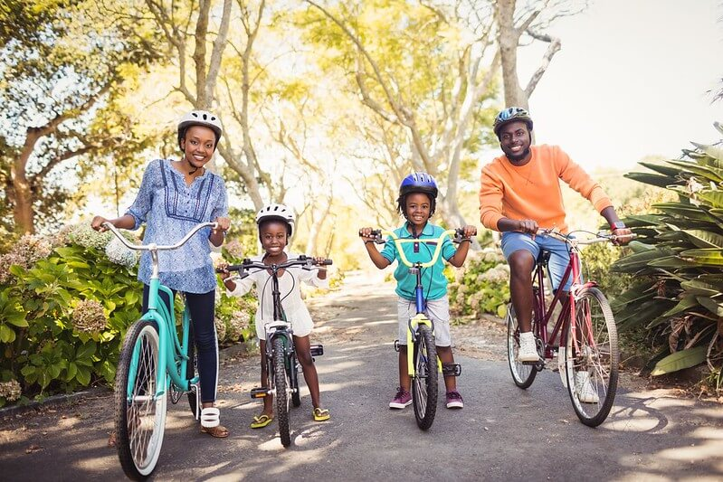 Family smiling as they ride their bikes.
