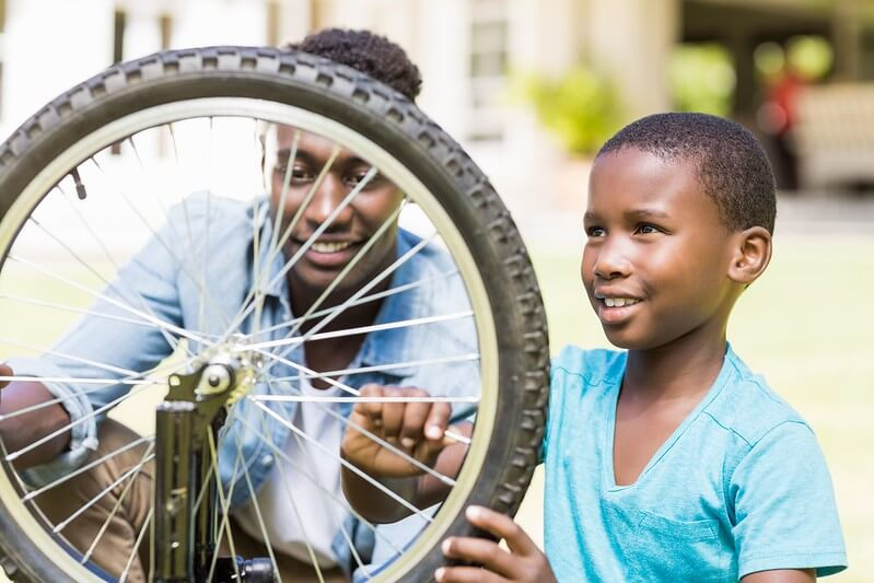 dad helping his son to fix a bike