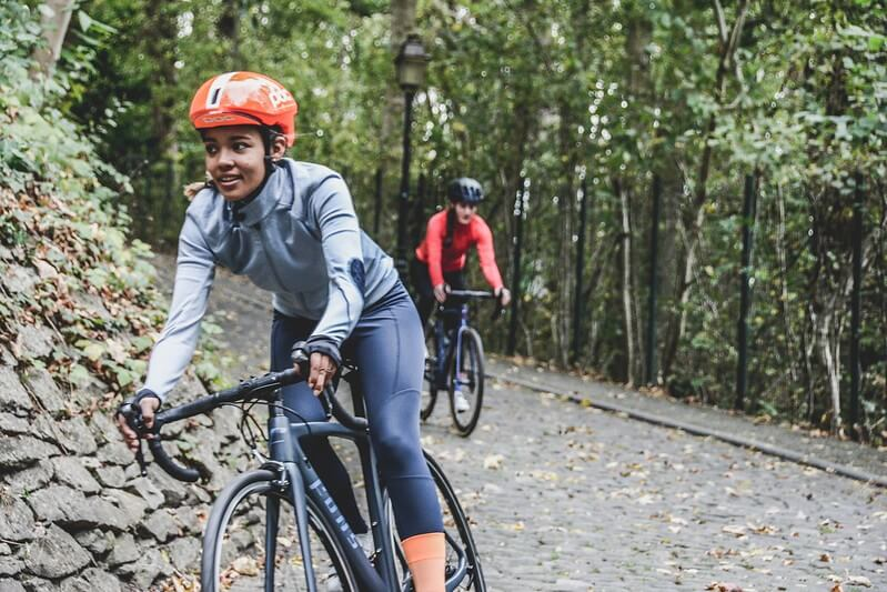 cyclists wearing helmets in a forest