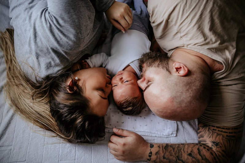 Photo of family laying on bed with their new baby, thinking about turkish boys' names