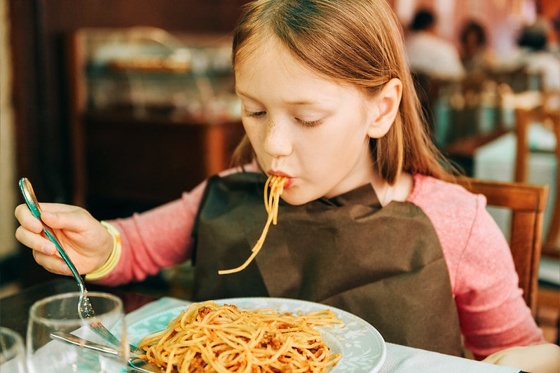 Girl eating spaghetti at a child-friendly restaurant