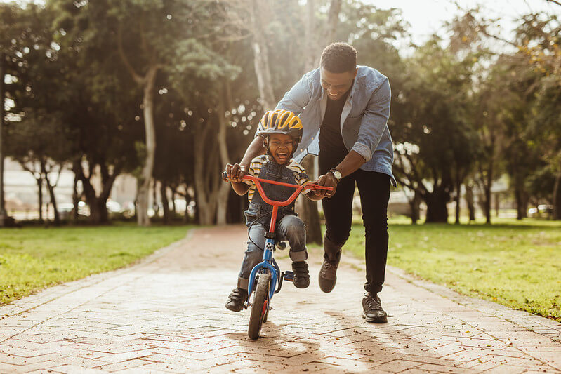 dad helping his son to ride a bike without stabilisers