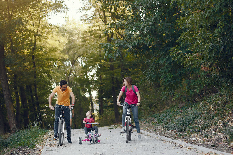 family riding their bikes in a forest
