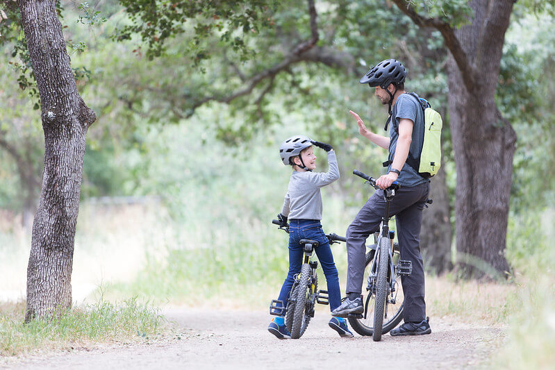 dad and son high-fiving on their bikes