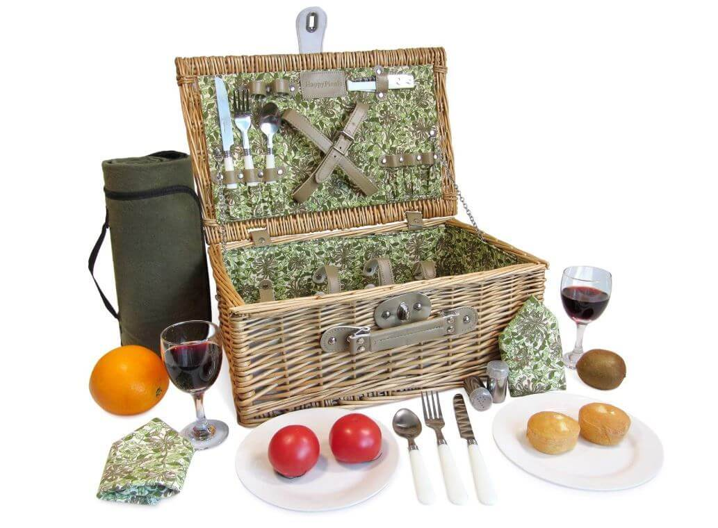 open floral picnic basket surrounded by plates and glasses