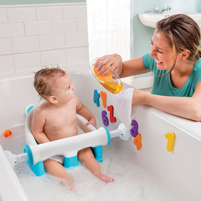 Boy in a baby bath seat during his baby bath playing with his mum.