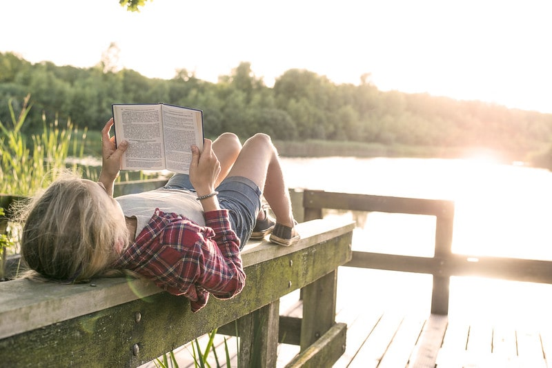 Teenager reading by lake while on a family holiday.