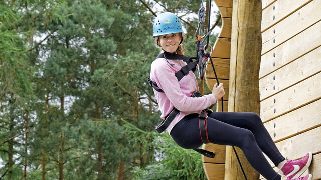 Girl abseiling at PGL while on family holiday with teenagers