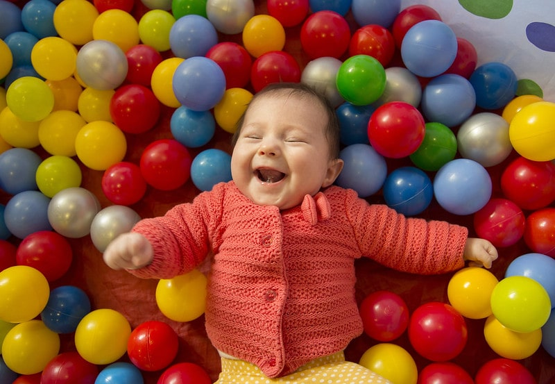 Baby laughing in a sensory ball pit min