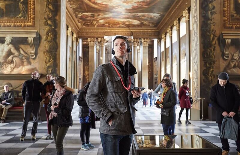 Man with audio guide on a tour of The Painted Hall.