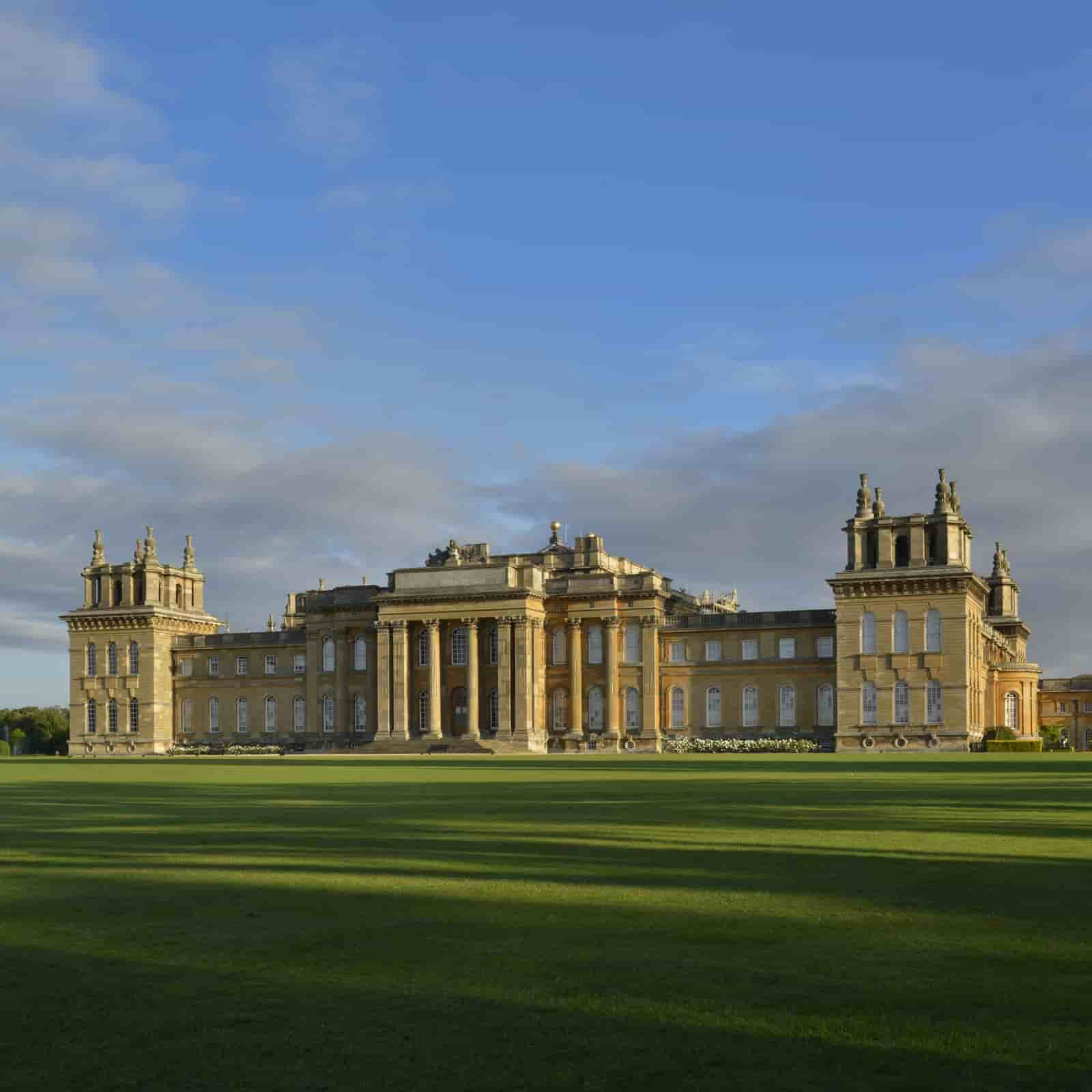 Blenheim Palace exterior against the blue sky, showing lush green acres in front.