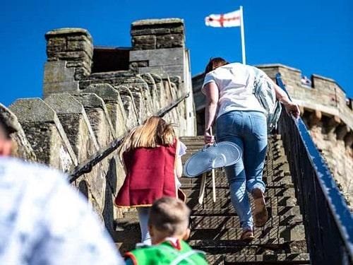 Family climb the ramparts of Warwick Castle.