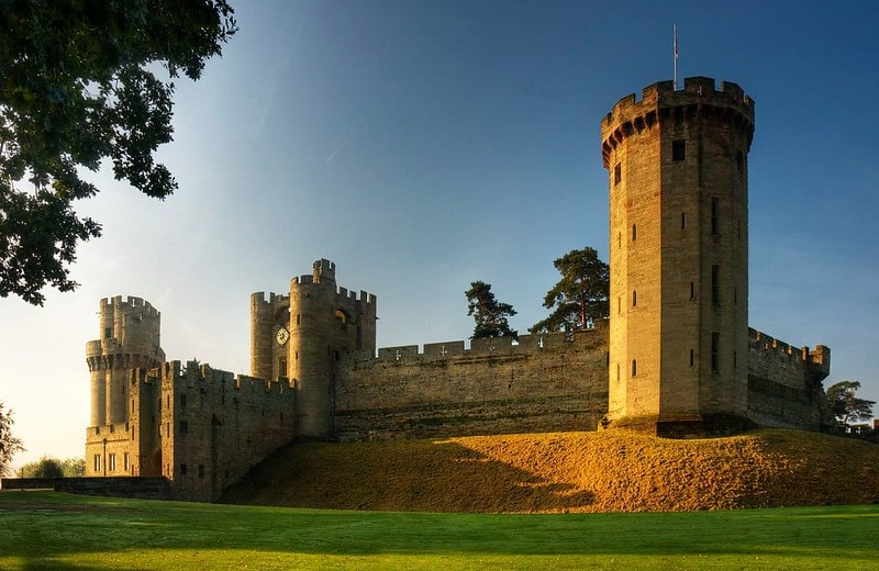 Close-up of Warwick Castle against the blue sky, sitting on its hill.