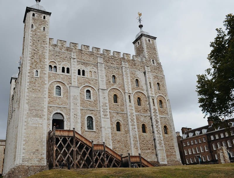 The Tower of London's White Tower against ominous cloudy sky.