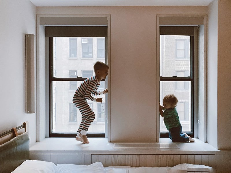 Two kids playing by the windows.