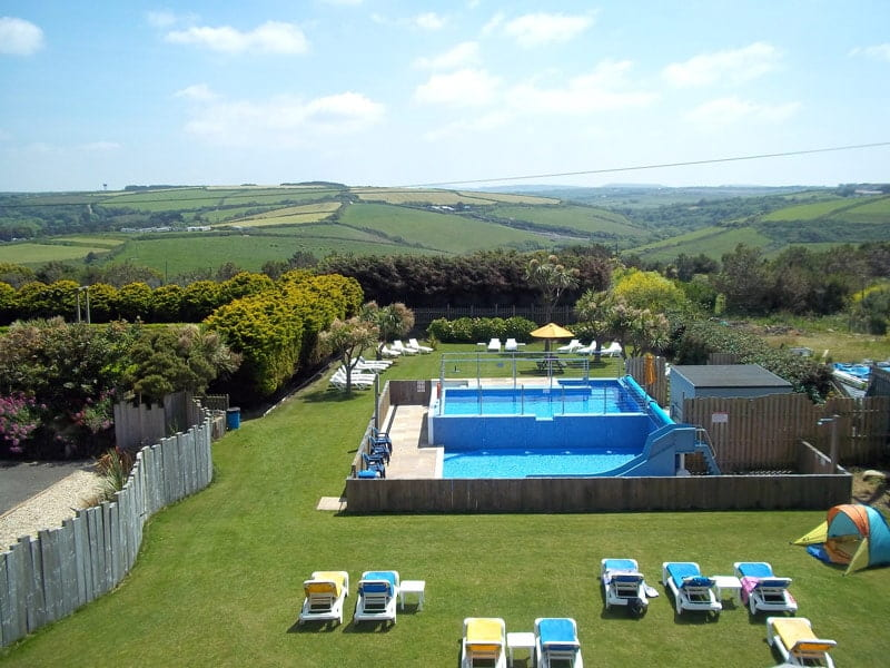 Outdoor pool with slide surrounded by green fields.
