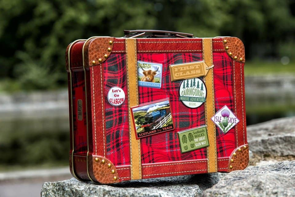 Tartan suitcase with badges of different areas in Scotland stuck on.