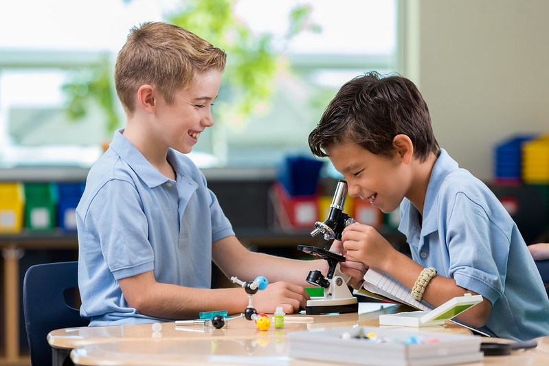 Two boys smile as they use a kids' microscope together.