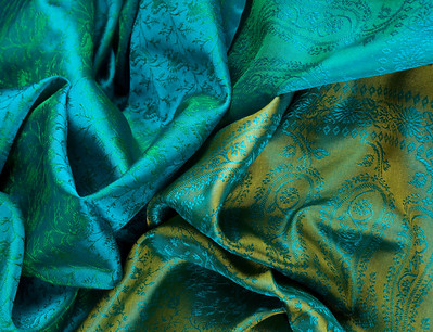 Green/blue coloured fabric draped in a messy pile.