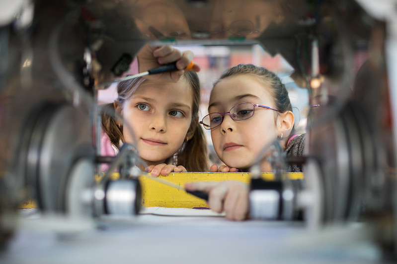 Two girls using screwdrivers to fix a metal contraption.