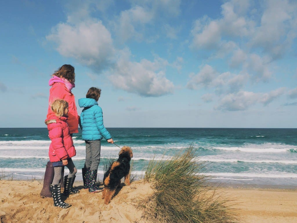 Family with a dog looking out at sea on the beach while staying in Cornwall.