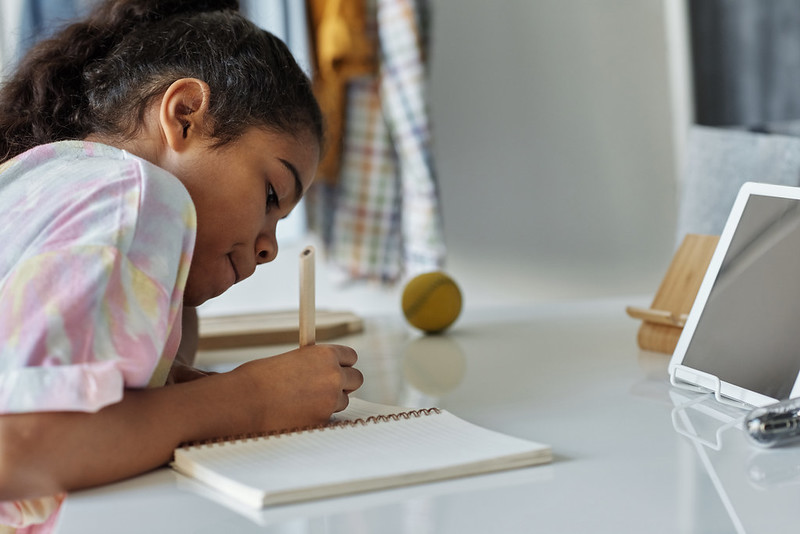 Young girl at her desk writing something into a notebook.