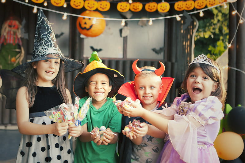 Four children in Halloween costumes are having fun at a Halloween party.