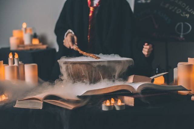 Wizard with their wand over a steaming cauldron. Surrounded by candles and a blackboard with spells in the background.