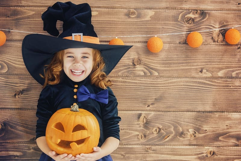 Little girl wearing a witch's hat holding a carved pumpkin for Halloween.
