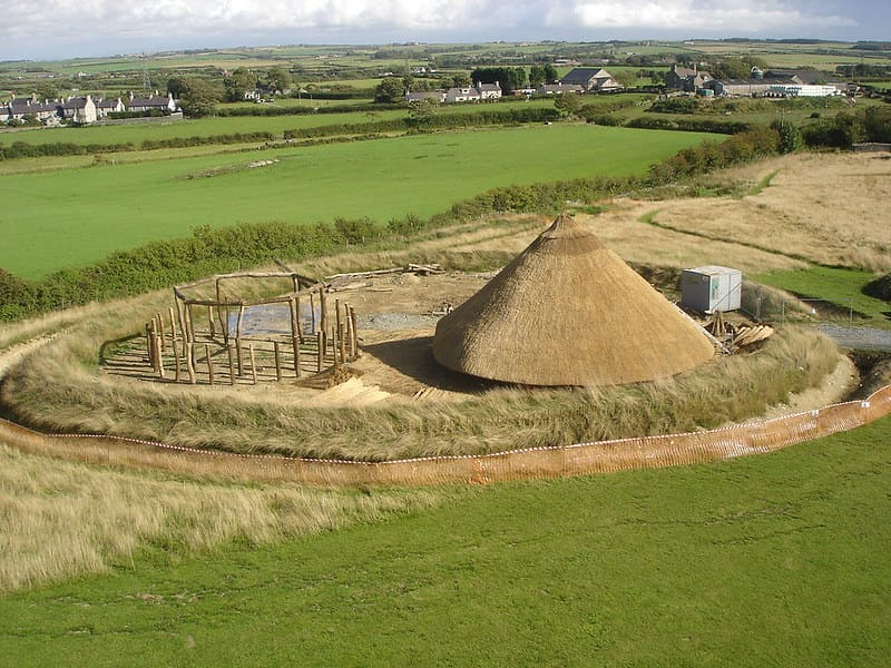 Celtic round house in centre with green fields surrounding the circular construction.