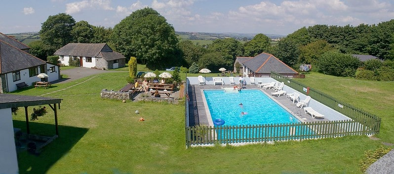 Outdoor pool set in a garden amongst rolling fields at Wringworthy Cottages, Cornwall.