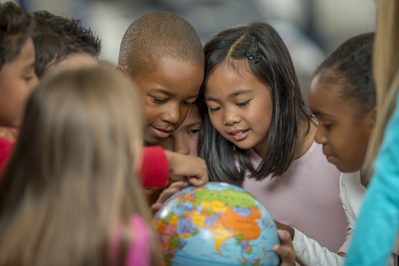 Group of children looking intently at a colourful globe.