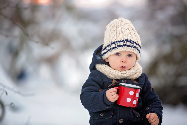 Child in a woolly hat holding a mug of hot chocolate in the snow