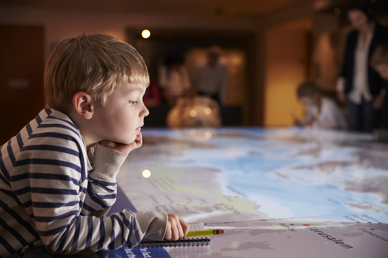 A KS2 child gazes intently at a large map.
