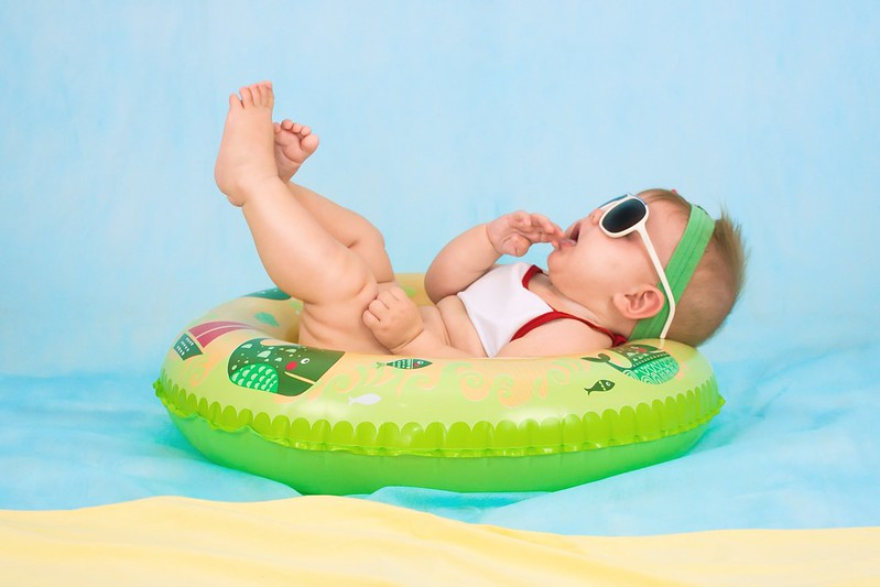 Baby wearing sunglasses with its legs in the air whilst lying in an inflatable ring on holiday.