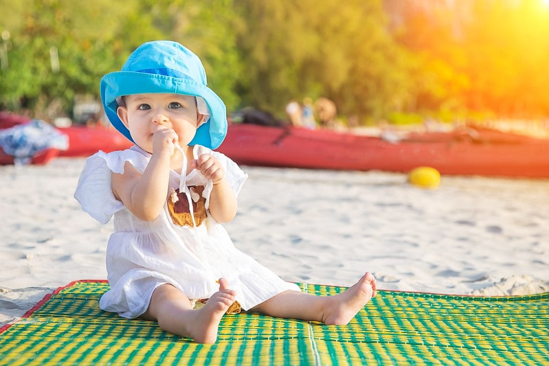 Baby wearing a blue sun hat sat on a rug on the beach on holiday.
