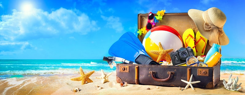 Suitcase filled with beach holiday essentials.
