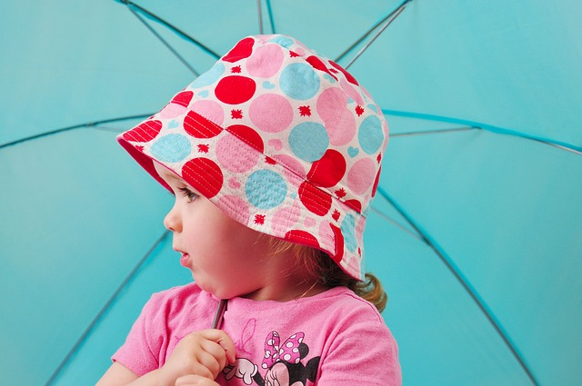Girl wearing a colourful spotty sun hat holding a blue umbrella on holiday in the UK.