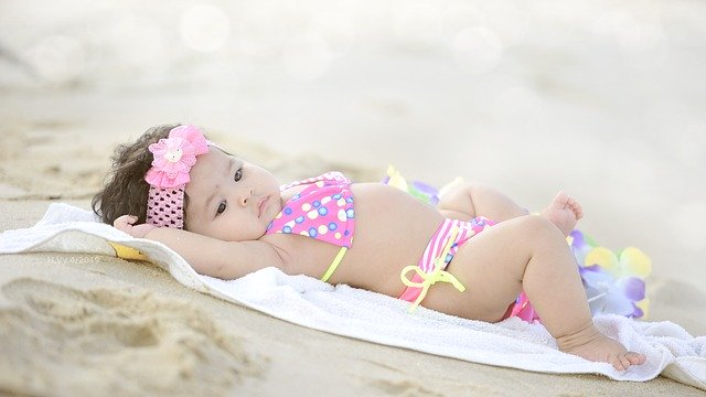 Baby wearing swimsuit lying on a towel in the sand on beach holiday.