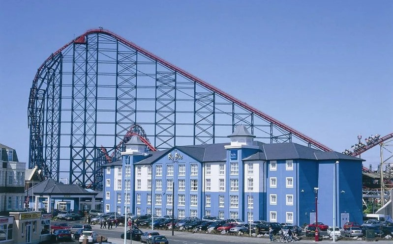 Front of the Big Blue Hotel, Blackpool, with a backdrop of the amusement park rollercoaster.