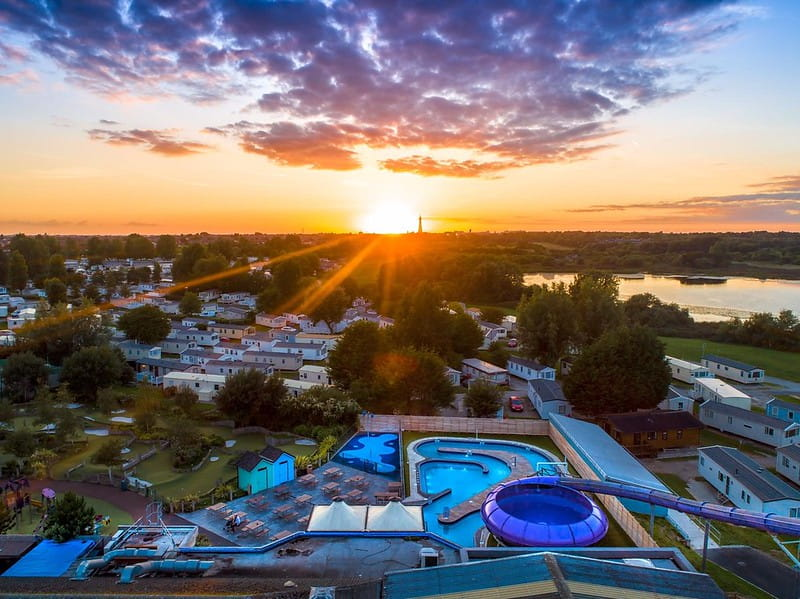Birdseye view of the outdoor pool with waterslides at sunset.