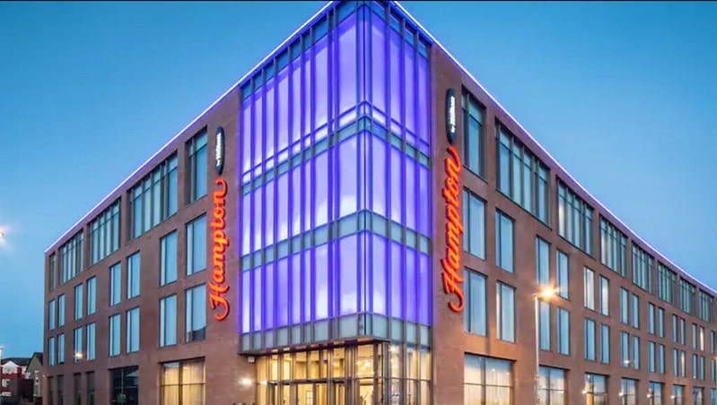 Modern front facade of Hampton by Hilton, Blackpool, lit up in the evening.