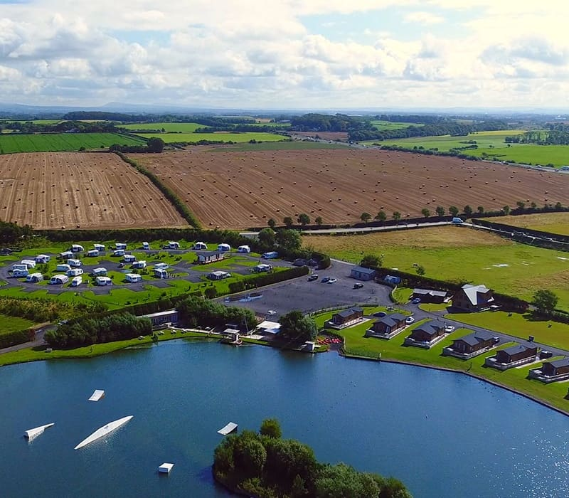 Birdseye view of the lakeside lodges surrounded by fields.