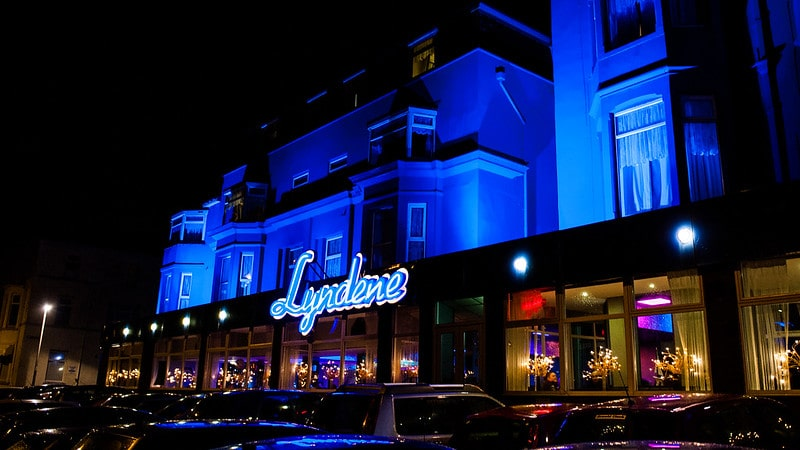 Front facade of the Lyndene Hotel, Blackpool, lit up in blue at night.