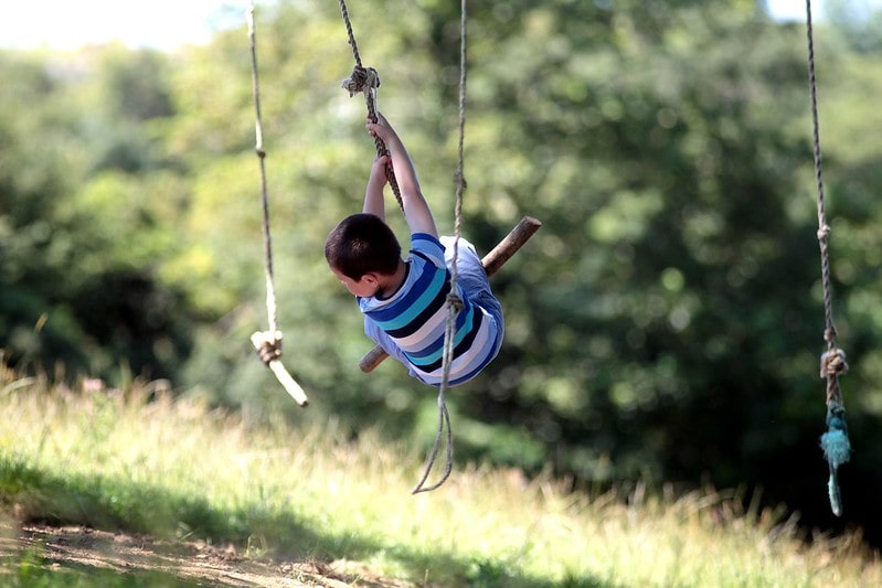 Boy on a swing outdoors at Trevella Holiday Park, Newquay.