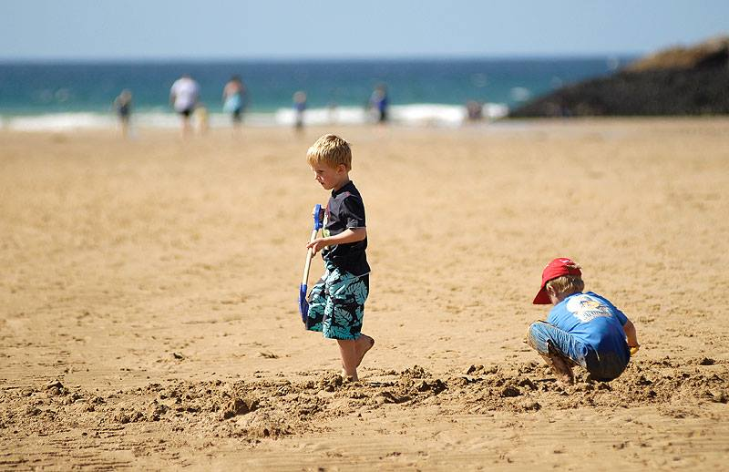 Boy holding a spade walking in the sand on a staycation at Porth Beach.