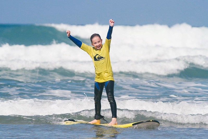 Girl with her hands in the air enjoying her success at paddle-boarding in Newquay.